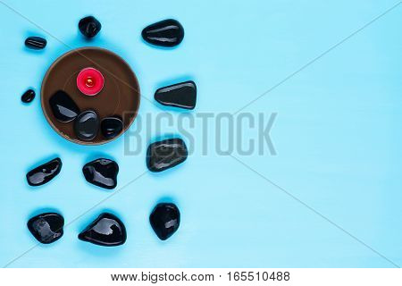 black stones in the corner and a lighted candle on a blue background with a place for inscription