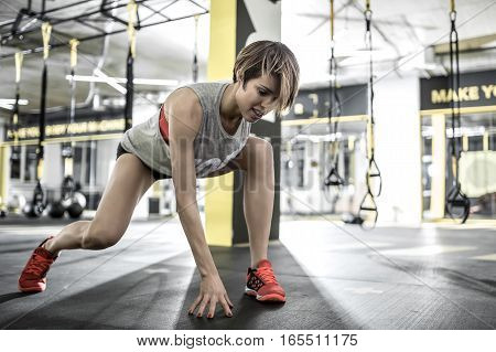 Cute smiling girl with does stretching in the gym on the background of the hanging TRX straps. She wears a red top and sneakers, gray sleeveless, black shorts. Horizontal.
