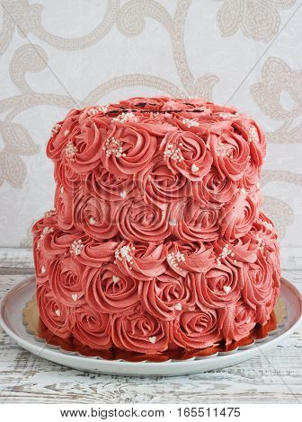 Gorgeous two-tier cake covered in roses made of butter cream icing sitting on a cake pedestal with background