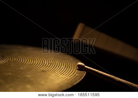 Close up shot of two drum sticks hitting a cymbal.