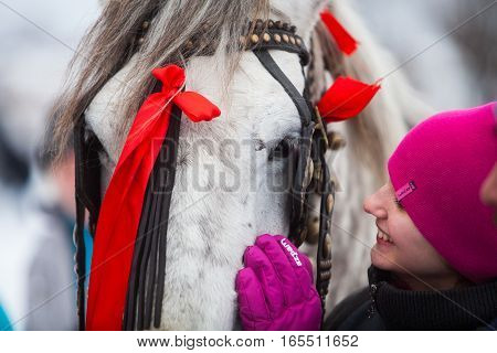 Pietrosani Romania - January 6 2017: A teenage girl pets a horse in Pietrosani Romania.