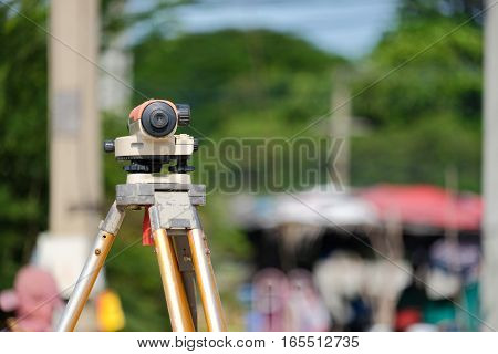Surveyor equipment tacheometer or theodolite outdoors at construction road against worker blur background