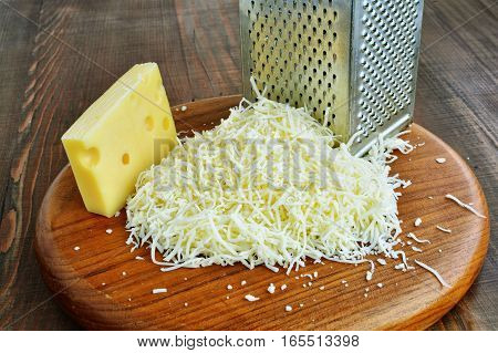 Emmental cheese is grated on wooden board