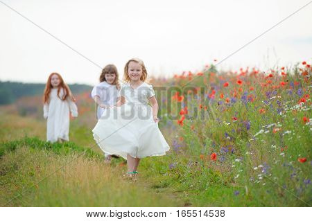 three girls in white dresses playing outdoors. Selected focus