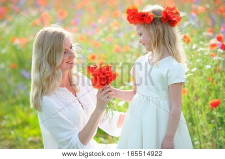Little beautiful pretty girl giving a flowers to her happy mother - outdoors
