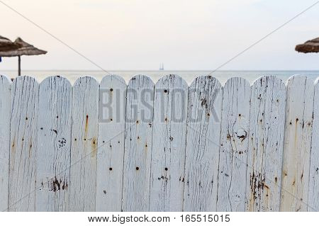 Private beach surrounded by white wooden fence