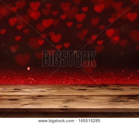 Red love heart in a dark background in front of a empty wooden table for a valentines day concept