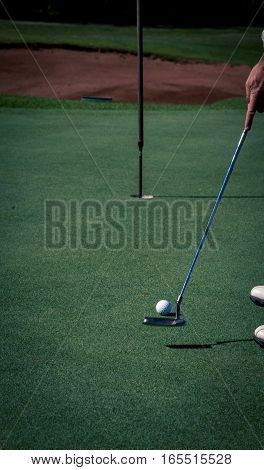 A left handed golfer putts the ball