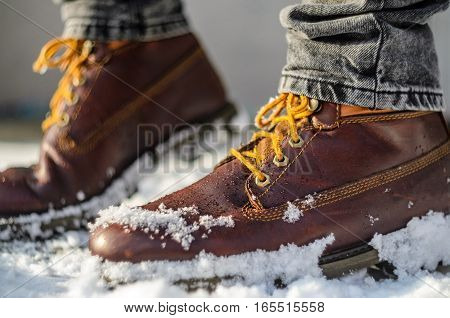 Brown leather shoes in the snow. Shoe Detail. Shallow depth of field. Legs in the warmth concept