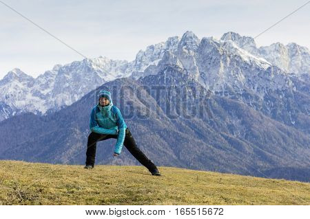 Active lifestyle - healthy lifestyle. Outdoor activities and meditating on the beautiful meadow. Mountain and high peaks in the background.