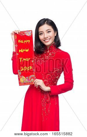 Portrait of a beautiful Asian woman on traditional festival costume Ao Dai showing New Year scrolls Tet holiday. Lunar New Year. Text mean Always Lucky.
