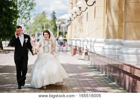 Walking Wedding Couple. Groom Speeking On Phone.