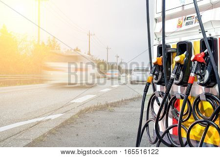 Gas Pump Nozzles In A Service Station Againt Truck Motion Blur Background