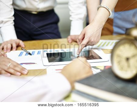 group of asian people meeting in office discussing business plan using tablet computer.