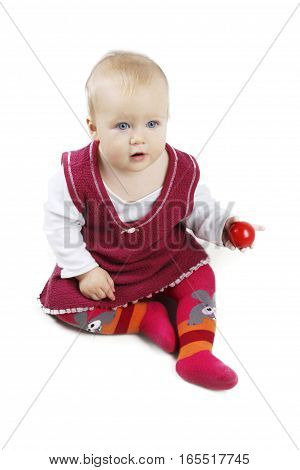 Adorable little baby girl in red dress sitting and playing with red ball - isolated over white background.