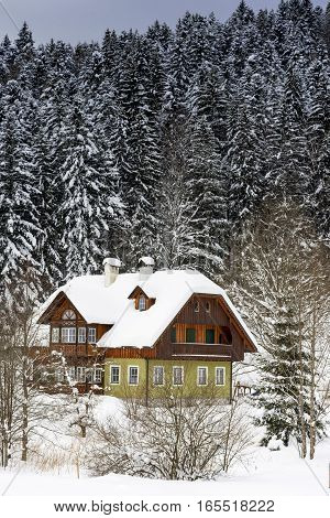 Wooden Mountain House in Winter Forest. Winter Idyll.