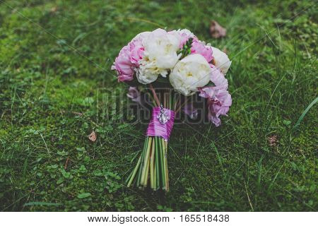 Wedding bouquet of peonies on the grass