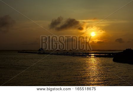 An evening sunset over a bay. There is a silhouette of a wooden pier in the foreground. The location is Northside park in Ocean City Maryland.