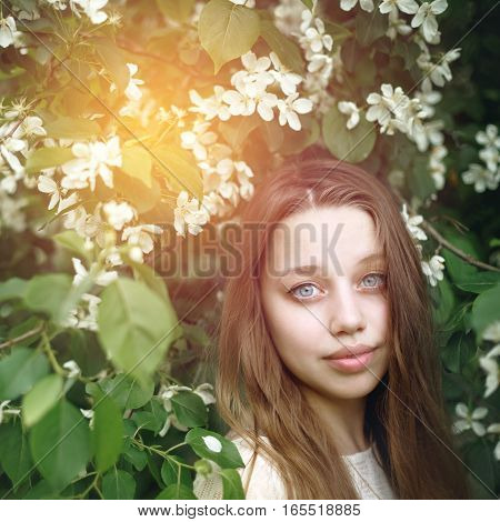 Portrait Of Young Woman In Blossoming Spring Tree
