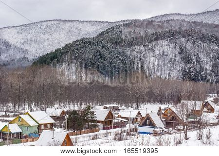 The settlement in the woody mountains brought by snow