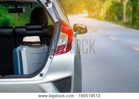 Close up of new silver hatchback car parking on local road with travel luggage, sunglasses and hat for travel concept