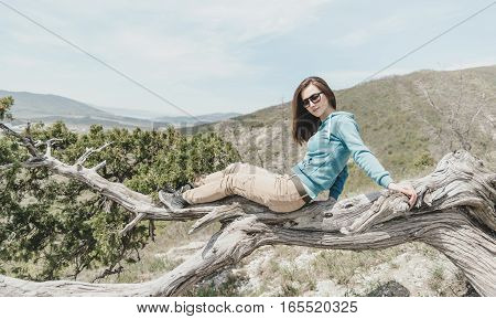 Beautiful girl in glasses resting on juniper tree outdoor looking at camera
