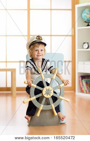 Kid dressed as a captain or sailor plays on chair as on ship in his room. Child boy rotates the wooden steering wheel.