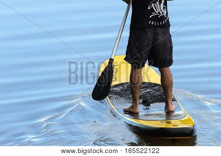 Londrina PR Brazil - December 24 2016: Man practicing Stand Up Paddle in the waters of Lake Igapó in Londrina PR Brazil.