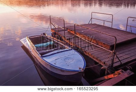 Old rowboat moored wooden pier amazing sunset lake river. Old rowboat prishvartovanaya to a wooden pier on the lake. A beautiful golden sunset on the river.