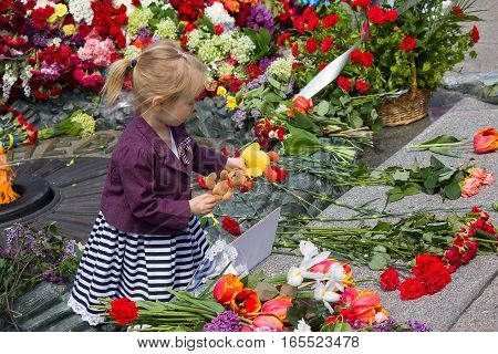 Kiev Ukraine - May 9 2015: Girl holds a toy at the monument to fallen soldiers of World War II