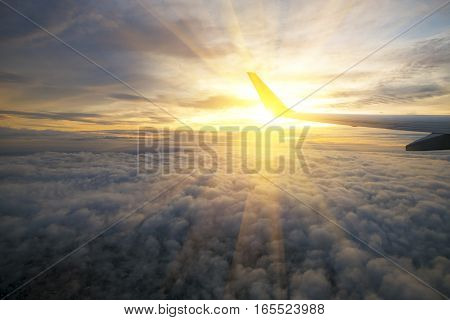 Wing of an airplane flying above the sunriseclouds