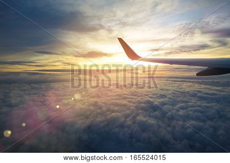 Wing of an airplane flying above the sunriseclouds and flare effect