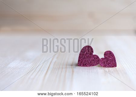 Two delicate pink heart standing next leaning on each other, Valentine's Day, Valentine's Day, on a wooden background