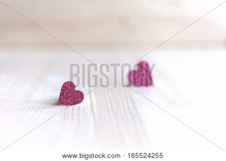 Two delicate pink heart are at a distance from each other on Valentine's Day, Valentine's Day, on a wooden background