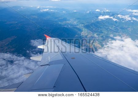 Wing of airplane with mountain and foggy from window view