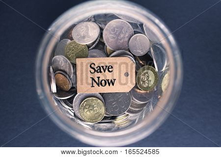 Saving Concept : Save Now label with coins in the glass