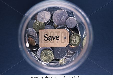 Saving Concept : Save label with coins in the glass