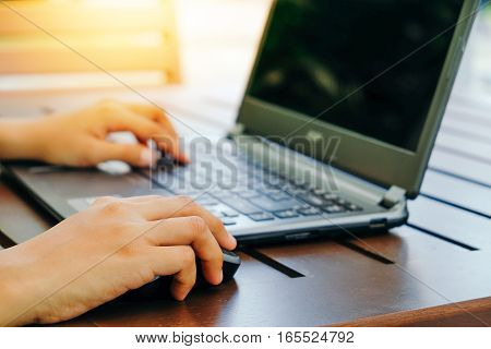 hands working on laptop with vintage tone
