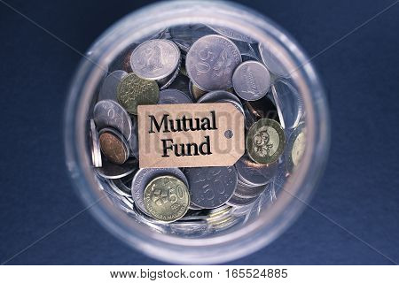 Saving Concept : Mutual Fund label with coins in the glass