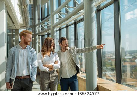 Group of businesspeople have quick informal business in the building and looking trough the window.