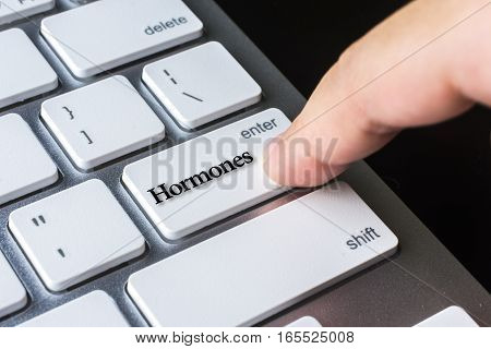 Finger on computer keyboard keys with Hormones word