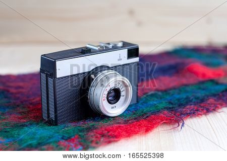 Old camera stands on the wooden boards on the old beautiful colored scarf, vintage, ancient