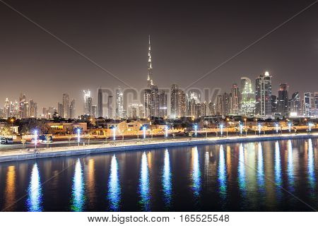 Skyline of Dubai city at night as seen from the new Water Canal. United Arab Emirates Middle East