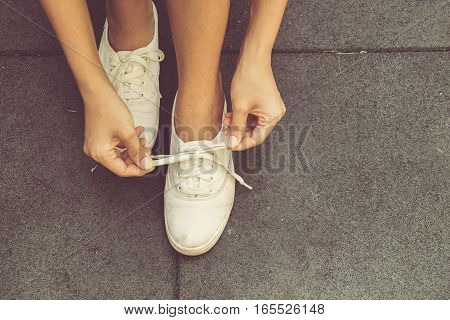 A young woman is tying the laces of her slip-ons shoes