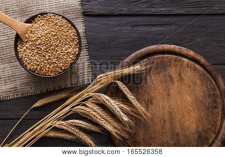 Bread baking background. Grain and ears scattered around on rustic wood near round wooden desk. Agricultural wheat harvest, bread making composition