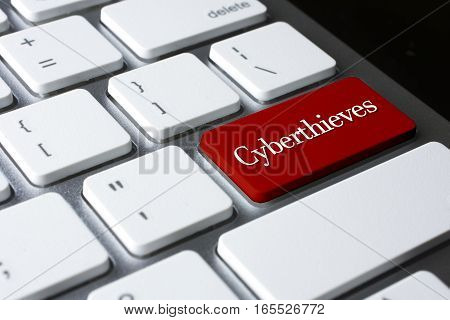 Cyber thieves word on red color enter keyboard