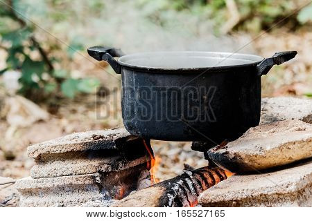 Old cooking pot stove using firewood in nature background.