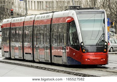 Modern city tramway drives through the city