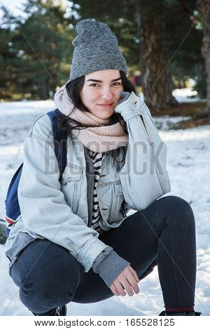 Young caucasian white woman with brown eyes wearing a cap and warm clothes in the snow. She enjoys a winter vacation trip in the snowy forest.
