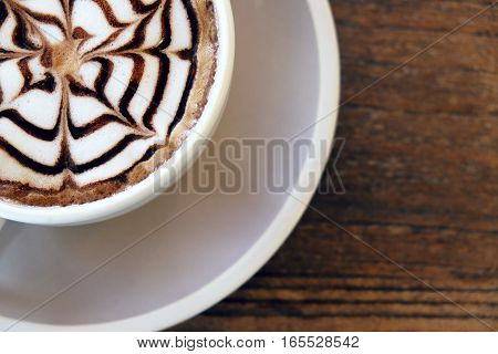 Mocha coffee (also called Caffe Mocha) with wooden saucer. Interior coffee shop. Main ingredients of mocha is chocolate espresso hot milk. (vintage tone)